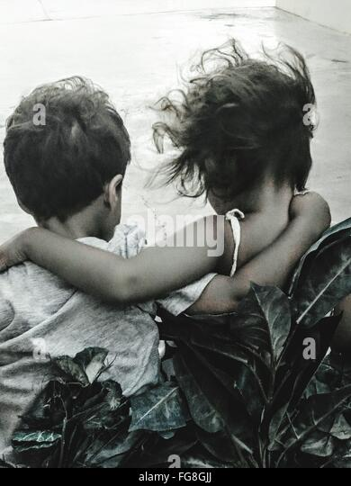 Rear View Of Siblings With Arm Around Outdoors - Stock Image