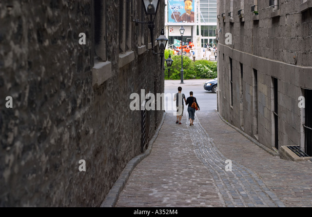 Couple holding hands walking down a romantic narrow street, with cobble-stone pavement. Montreal, Quebec, Canada. - Stock Image