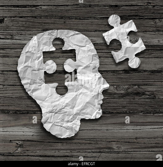 Puzzle head brain concept as a human face profile made from crumpled white paper with a jigsaw piece cut out on - Stock Image