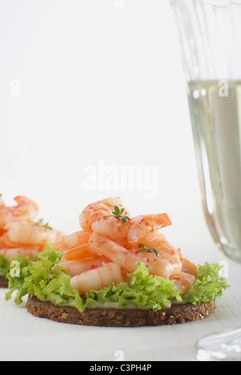 Prawns on pumpernickel with salad and glass - Stock-Bilder