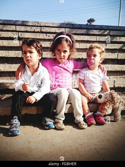 Happy Siblings Sitting On Steps - Stock Image