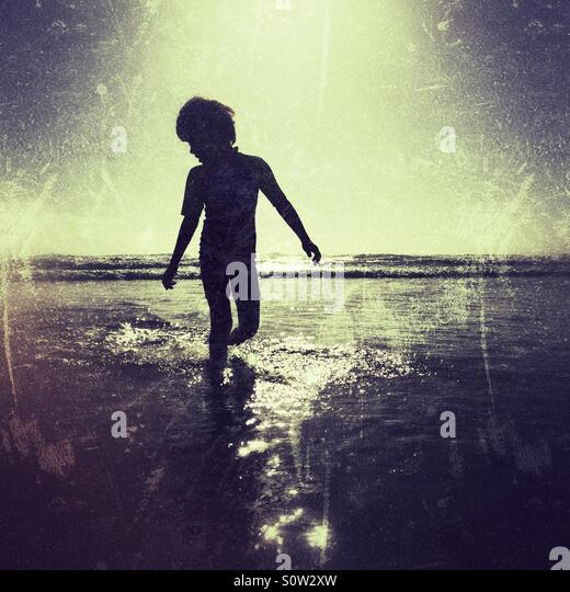 Silhouette of boy on beach - Stock Image