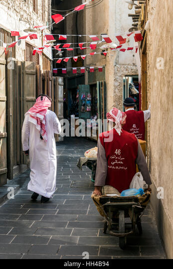 Traditionally dressed Arab man walking in the Souq Waqif, Doha, Qatar - Stock Image