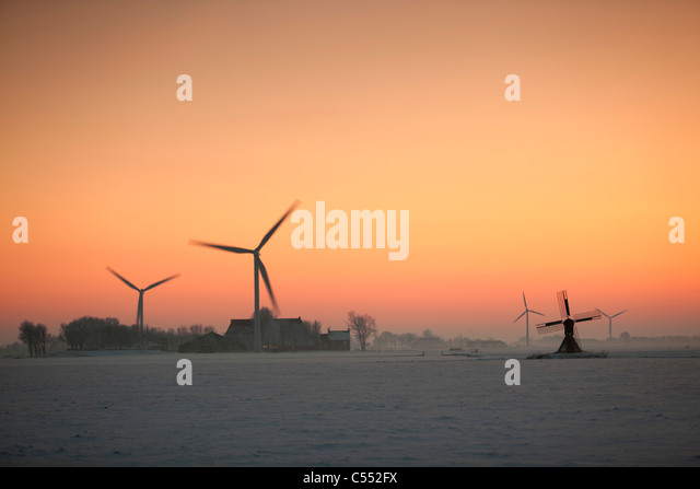 The Netherlands, Tritzum, Small traditional windmill, wind turbines and farm in snow at sunset. - Stock Image
