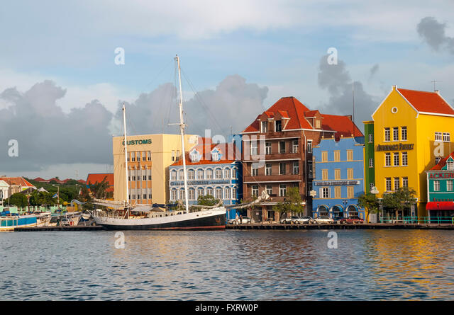 Dutch architecture and cafes line the waterfont on the Punda side of Willemstad Curacao - Stock Image