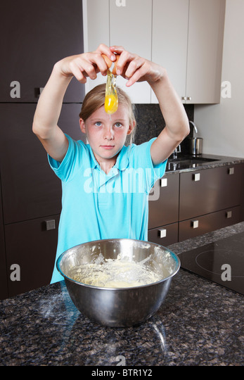 Girl breaking and egg over mixing bowl - Stock Image