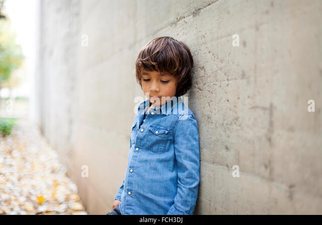 Portrait of sad little boy wearing denim shirt leaning against concrete wall - Stock Image