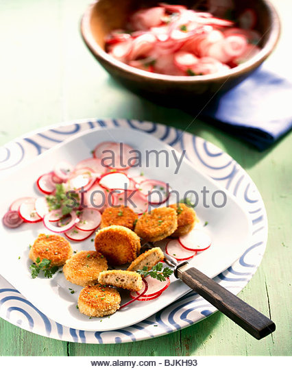 Breaded, fried slices of white sausage with radish salad - Stock Image