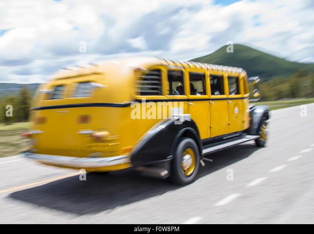 Motion blur of Yellowstone Tour Bus on the road in Lamar Valley, Yellowstone National park, Wyoming, USA - Stock Image