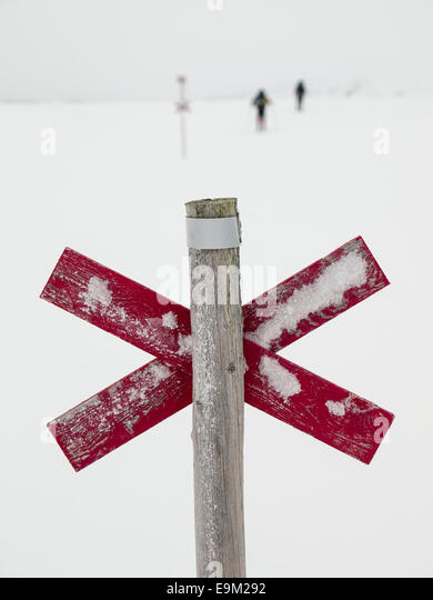 wooden trail marker next to ski trail in Northern Swedish mountain area of Sylarna (sylan) with  snowshoer out of - Stock Image