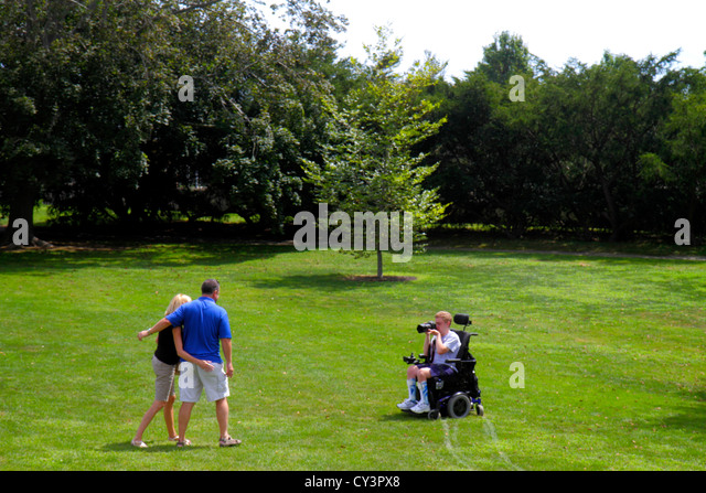 Rhode Island Newport The Breakers lawn family man woman father mother teen boy taking picture camera disabled electric - Stock Image