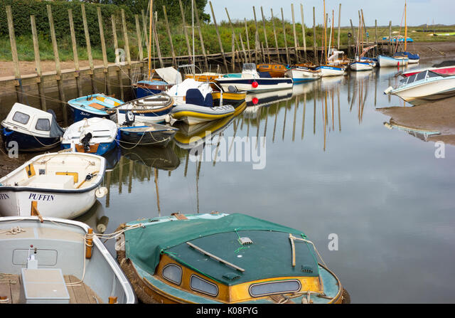Boats moored in Blakeney harbour with the tide out - Stock Image