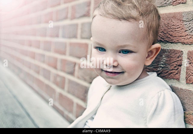 Beautiful Baby Girl against Brick Wall - Stock Image