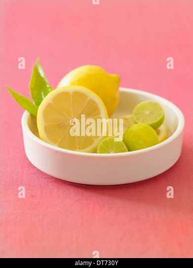 A contemporary white bowl with lemons and limes on a pink fabric background. - Stock Image