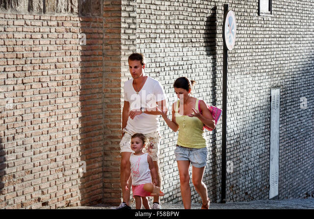Toledo Spain Europe Spanish World Heritage Site historic center brick wall man woman girl child mother father daughter - Stock Image