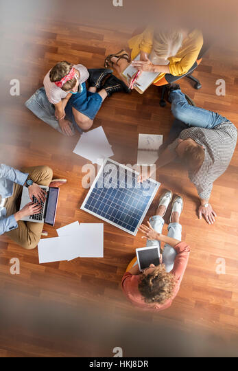 Overhead view designers brainstorming on floor in meeting - Stock-Bilder