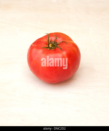 Whole red tomato on white background - Stock Image