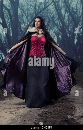 Woman throwing back cape standing on tree covered foggy path - Stock-Bilder