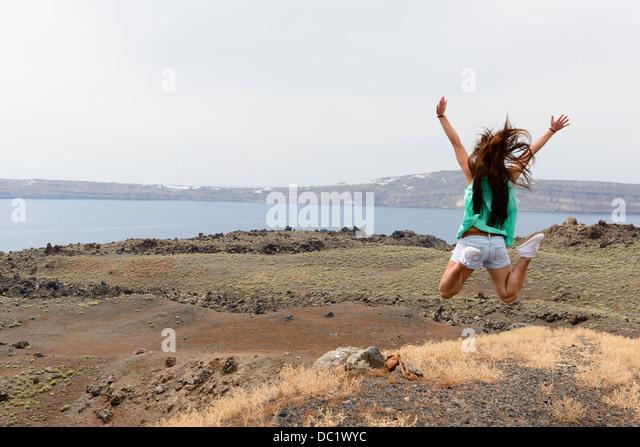 Female tourist jumping mid air, Santorini, Greece - Stock-Bilder