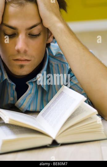 Young man reading book - Stock Image