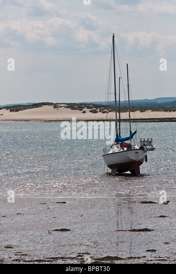 Boat beached at low tide - Stock Image