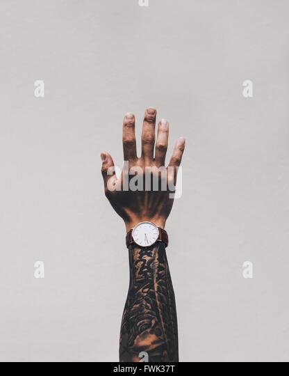 Cropped Image Of Man Hand With Tattoo Wearing Wrist Watch Against White Background - Stock-Bilder