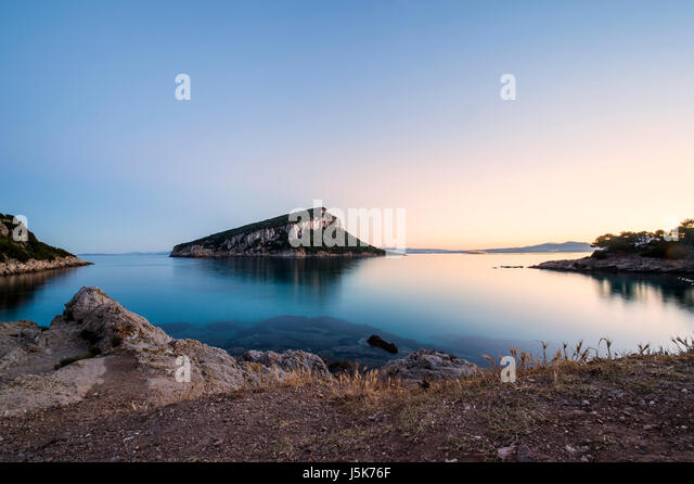 Sunset over a little island in Sardinia, Italy - Stock Image