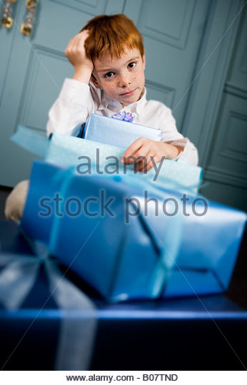 ginger haired boy with lots of presents - Stock Image