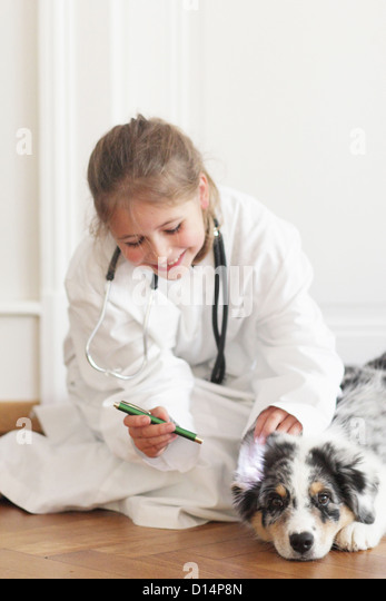 Girl playing doctor with dog - Stock Image
