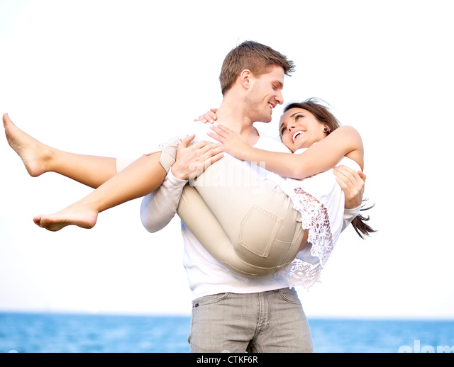 Portrait of a romantic guy looking affectionately at his girlfriend while carrying her - Stock-Bilder