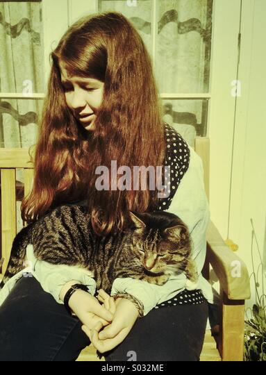 Girl with cat, teenager aged 14-16 years sitting outdoors with tabby cat on her lap - Stock Image