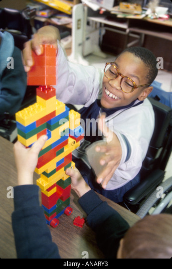 New Jersey East Orange Cerebral Palsy Center disabled student female therapist Black boy building blocks - Stock Image