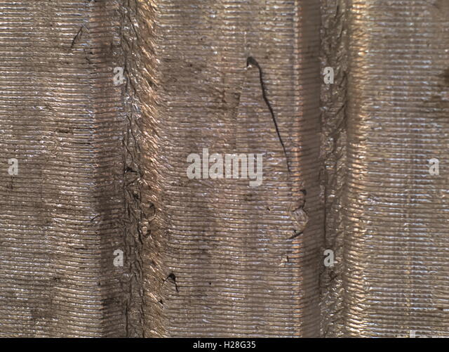 decayed corrugated tin foil sheet with scratches and dirt - Stock Image