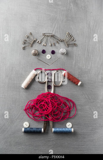 Sewing items building figur of a smiling girl on grey background - Stock Image