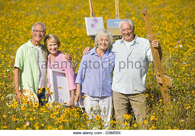 Portrait of smiling couples with paintings and easels among wildflowers in sunny meadow - Stock-Bilder