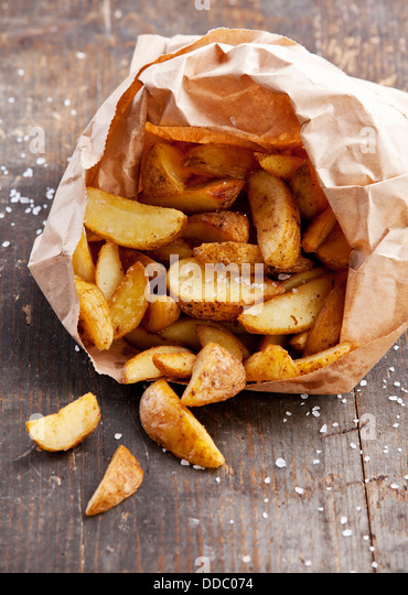 Fried potato 'country-style' in paper bag - Stock Image