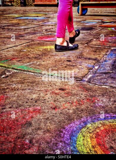 Young girl walking on pavement covered with child's chalk drawings - Stock-Bilder