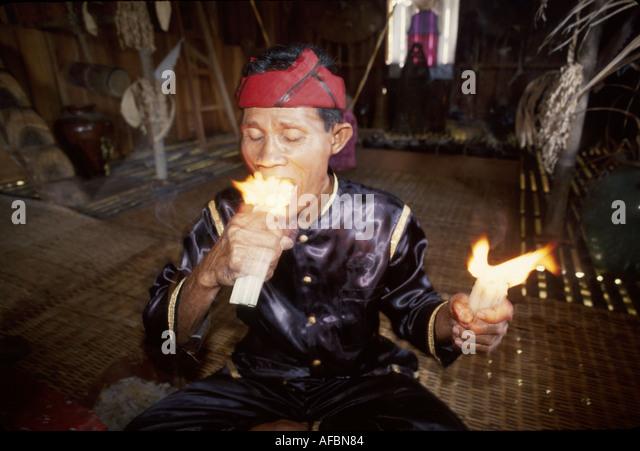 Malaysia Borneo Sarawak Kuching Cultural Village Melanau witch doctor swallows fire longhouse - Stock Image
