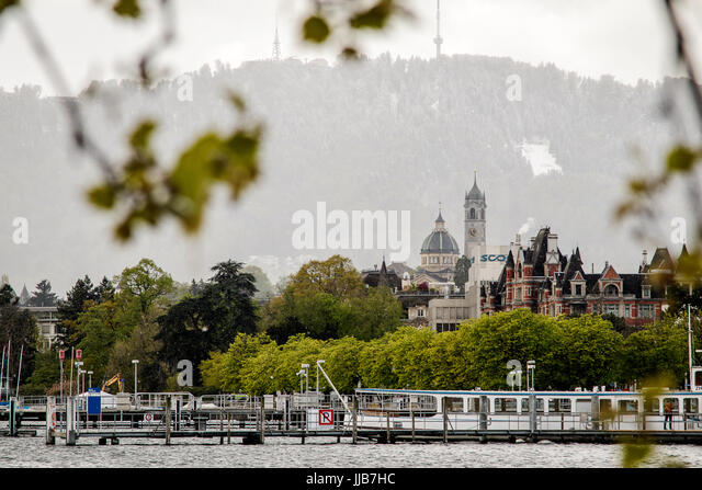 Snow falls and sun shines looking west from the eastern shore of Lake Zurich with Uetliberg in the background - Stock Image