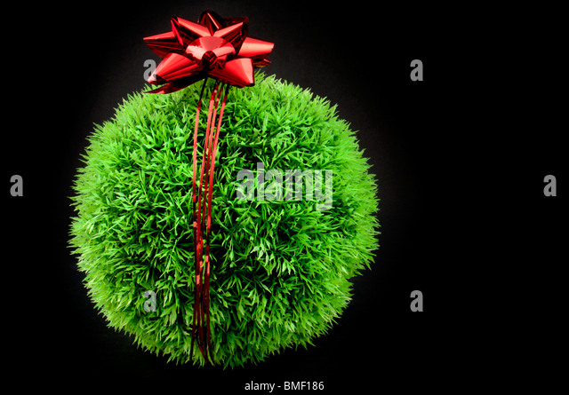 Green grass ball with red bow and ribbon over it, a gift fot the earth - Stock Image