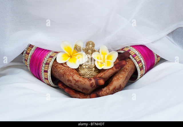 Indian girl wearing white silk sari with henna hands holding a Frangipani flower and a statue of Ganesha - Stock-Bilder