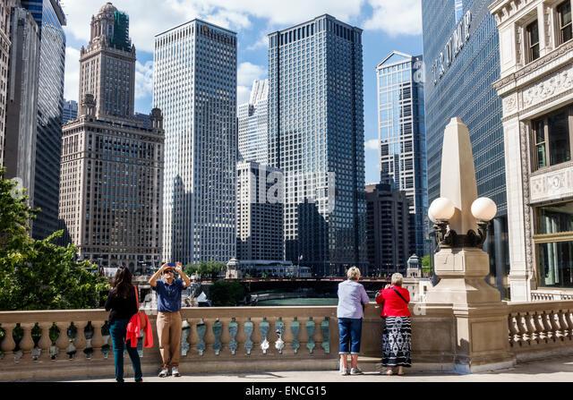 Chicago Illinois Michigan Avenue Chicago River skyline skyscraper architecture Wrigley Plaza balustrade man woman - Stock Image