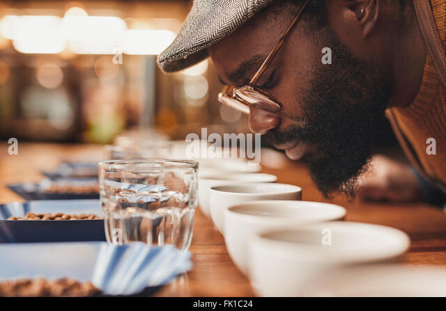 African man enjoying the aroma of fresh coffee at tasting - Stock Image