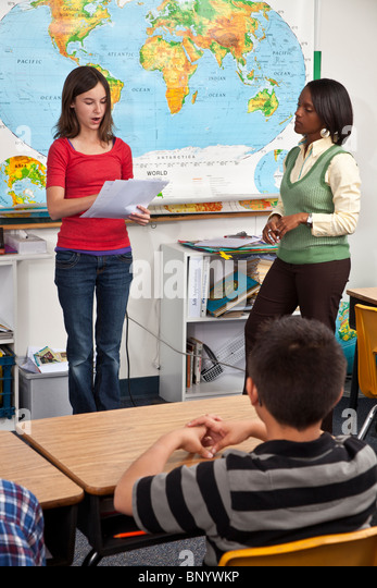 multi ethnic racial diversity racially diverse multicultural cultural interracial inter reading in front of class. - Stock Image