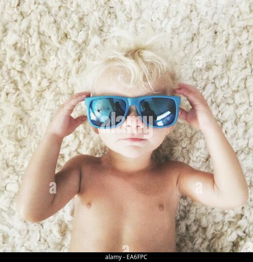 Boy lying on carpet wearing sunglasses - Stock-Bilder