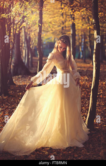 Beautiful woman with victorian dress in sunset light. Autumn leaves - Stock-Bilder