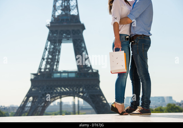 Young couple embracing in front of Eiffel Tower, Paris, France - Stock Image