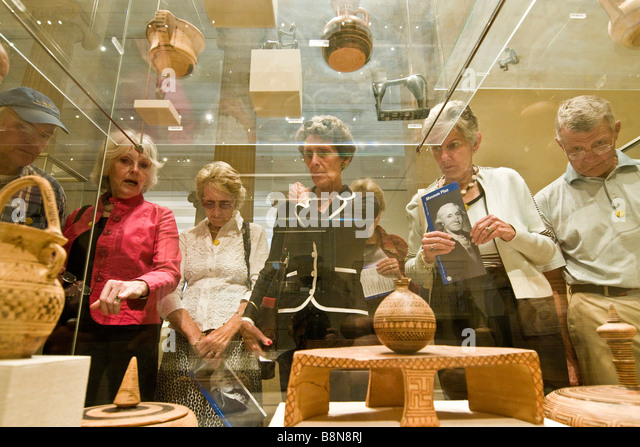 Visitor viewing a collection of items of classical antiquity, Metropolitan Museum of Art - Stock Image