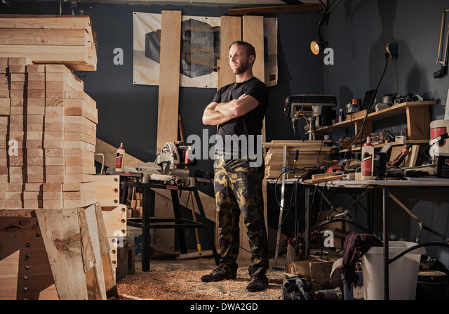 Portrait of mid adult man in carpenter workshop - Stock Image