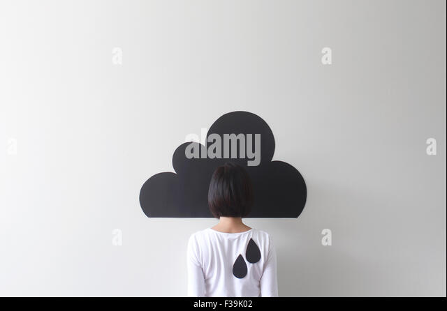 Rear view of a woman standing against conceptual rain cloud - Stock Image